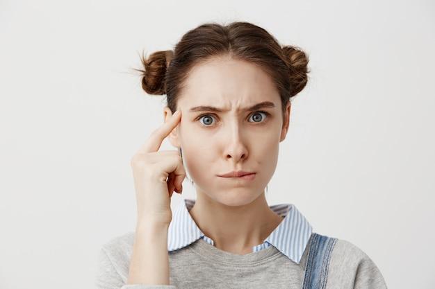 Mulher caucasiana pensativa em casual segurando o dedo no templo dela posando com olhar significativo. jovem fêmea tendo confuso emoções pensativas, ponderando sobre seu estilo de vida