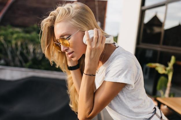 Mulher caucasiana pensativa em fones de ouvido brancos, ouvindo música ao ar livre.