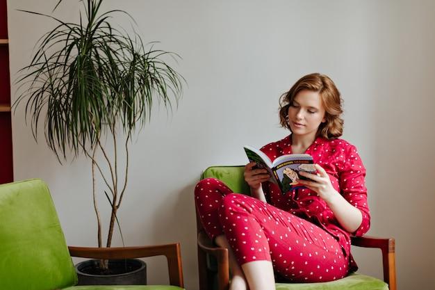 Mulher caucasiana pensativa em livro de leitura de pijamas. jovem encaracolada de pijama vermelho relaxando na poltrona.