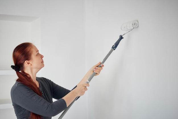 Mulher caucasiana, pintando com um rolo as paredes do apartamento.