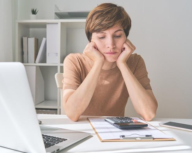 Mulher caucasiana planejando pagar contas e economizando dinheiro para gastar com sabedoria quando os preços aumentarem