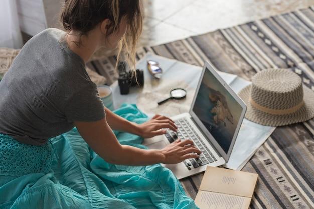 Mulher caucasiana planejando viagens de férias com laptop e internet em casa, lendo blog turístico on-line na internet enquanto relaxa no chão