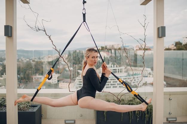 Mulher caucasiana praticando corda dividida alongamento na cobertura da casa