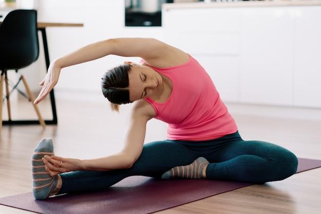 Mulher caucasiana, praticando ioga em casa