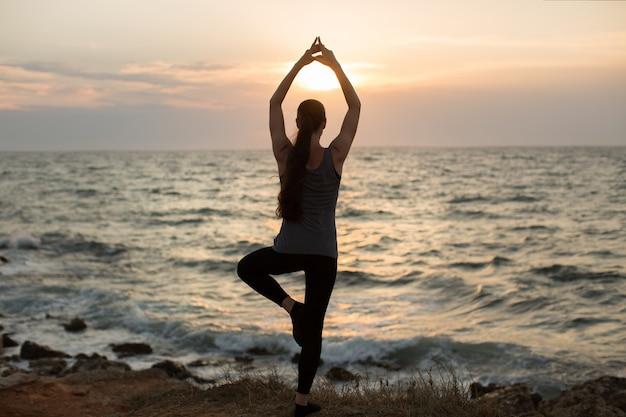 Mulher caucasiana, praticando ioga na beira-mar do oceano