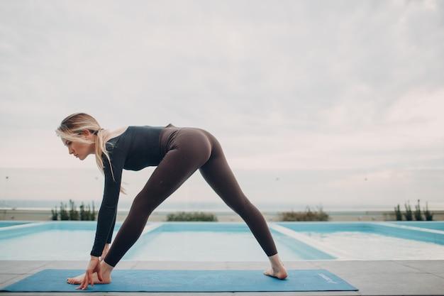 Mulher caucasiana praticando ioga na piscina e céu nublado