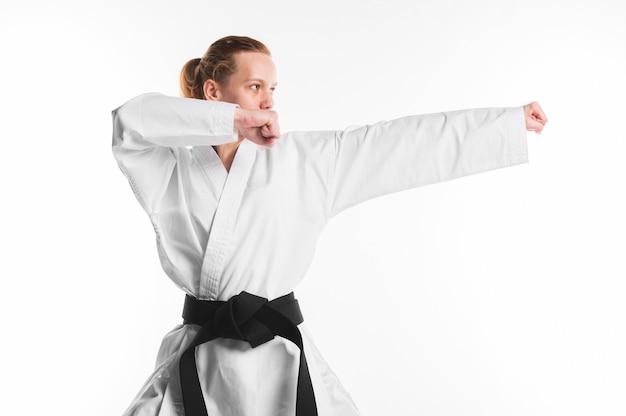 Mulher caucasiana, praticando karatê tiro médio