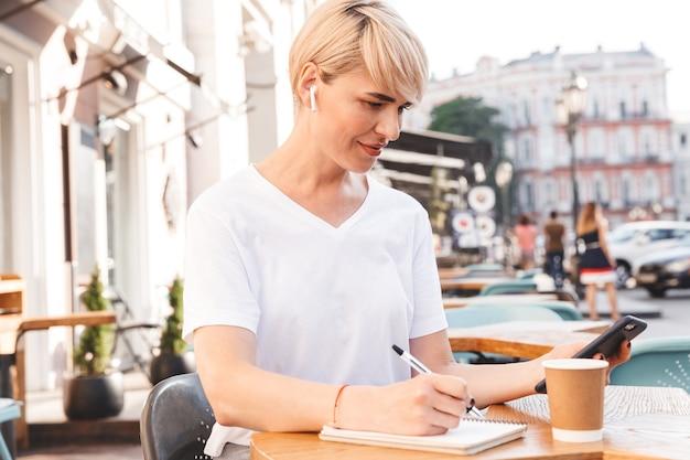 Mulher caucasiana, profissional, vestindo uma camiseta branca, sentada em um café de verão ao ar livre, enquanto escreve no caderno usando telefone celular e fone de ouvido sem fio