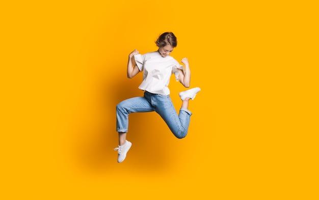 Mulher caucasiana pulando de jeans e camiseta branca, sorrindo e anunciando algo em uma parede amarela