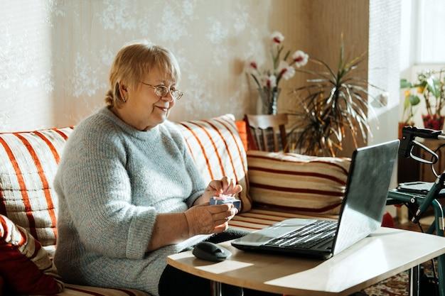 Mulher caucasiana real madura sênior olhando para a tela do laptop em casa e segurando uma caixa de presente feliz