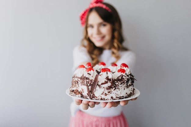 Mulher caucasiana refinada mostrando saboroso bolo com frutas. retrato interior de uma deslumbrante aniversariante com torta cremosa.