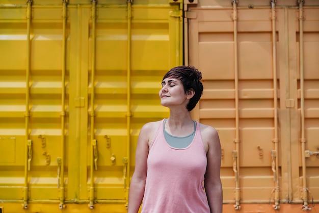 Mulher caucasiana relaxada com os olhos fechados sobre fundo amarelo. horário de verão. estilo de vida ao ar livre