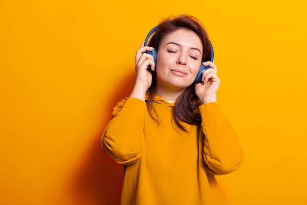 Mulher caucasiana relaxada curtindo música em fones de ouvido