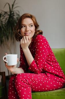 Mulher caucasiana romântica bebendo café da manhã. tiro interno de mulher jovem refinada de pijama vermelho, sentada na poltrona.