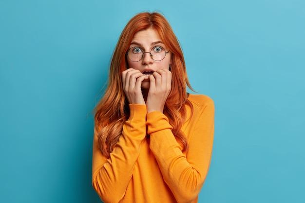 Mulher caucasiana ruiva surpresa e perplexa morde as unhas mantém a boca aberta engasgando de espanto vestida com um macacão casual.