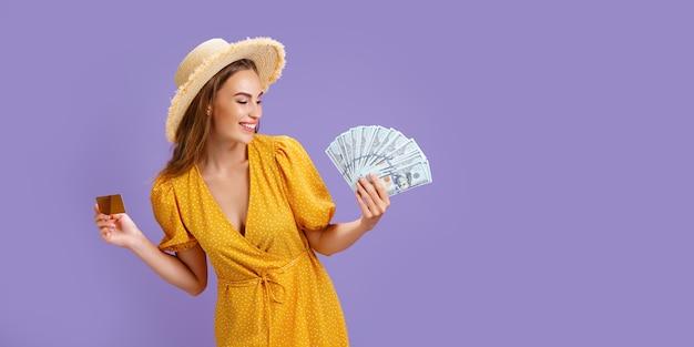 Mulher caucasiana s usando chapéu de palha, segurando o cartão de crédito e fã de dinheiro do dólar isolado sobre o roxo.