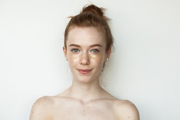 Mulher caucasiana sardenta com cabelo vermelho usando tapa-olhos de hidrogel, posando em uma parede branca com ombros nus
