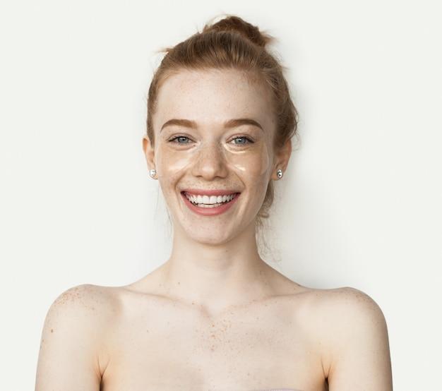 Mulher caucasiana sardenta com ombros nus e cabelo ruivo sorrindo para uma câmera em um fundo branco