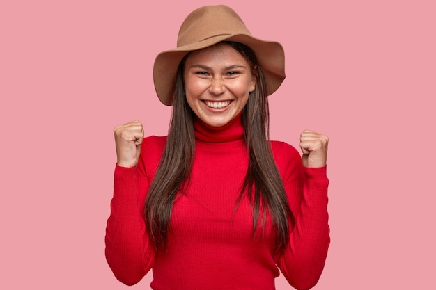 Mulher caucasiana sardenta e alegre levantando os punhos cerrados