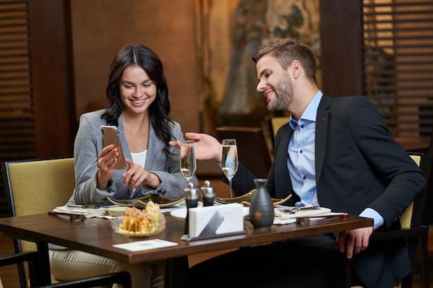 Mulher caucasiana satisfeita apontando o dedo para a tela do smartphone enquanto apresenta imagens para um homem interessado na mesa