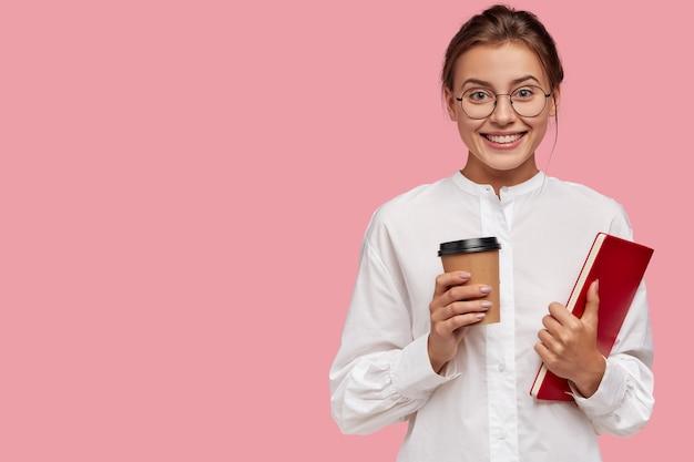 Mulher caucasiana satisfeita com expressão alegre, carrega café e livro para viagem, tem expressão positiva