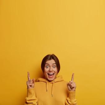 Mulher caucasiana satisfeita e alegre aponta acima, tem expressão alegre, mostra boa oferta, dá recomendação para subir escadas, usa moletom amarelo confortável, envolvida em campanha publicitária