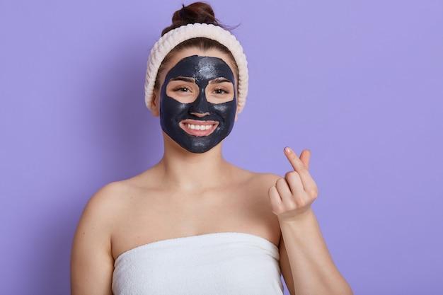 Mulher caucasiana satisfeita faz procedimentos de limpeza com máscara cosmética preta, limpa os poros, mostra os ombros nus, faz sinal com a mão coreana, expressa amor, faz gestos semelhantes