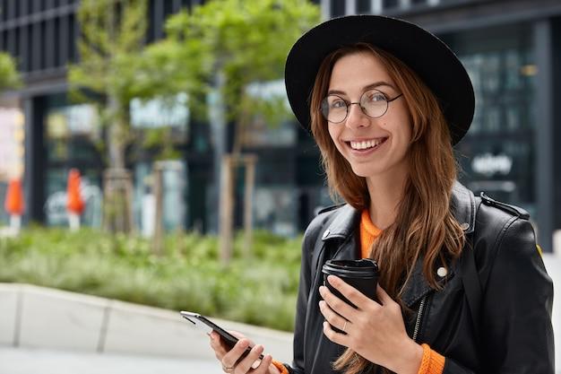 Mulher caucasiana satisfeita verifica o saldo da conta ou navega nas redes sociais, bebe café para levar