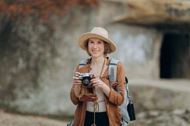 Mulher caucasiana saudável ativa, tirando fotos com uma câmera de filme vintage em uma floresta de pedras