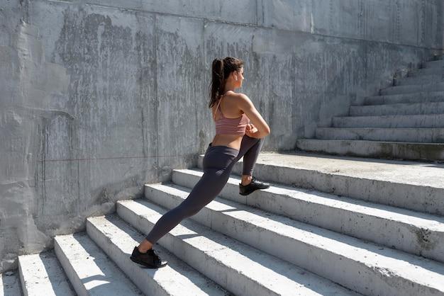 Mulher caucasiana se alongando antes de se exercitar