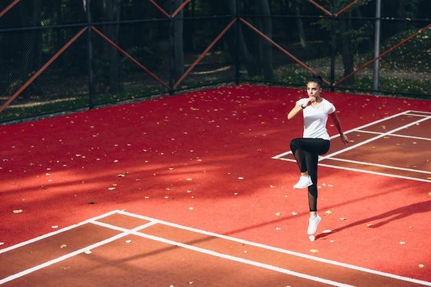 Mulher caucasiana se alongando em um estádio vermelho em um dia ensolarado fazendo exercícios para perder peso