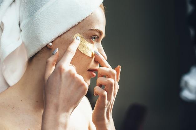 Mulher caucasiana se concentra na aplicação de tapa-olhos de hidrogel sob os olhos em casa, em um dia de spa