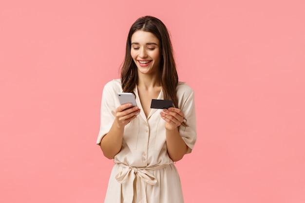 Mulher caucasiana sedutora sorridente despreocupada, comprar on-line, inserir o número do cartão de crédito, enviar pagamento, fazer compras na internet, segurando o smartphone e procurando o gadget, rosa