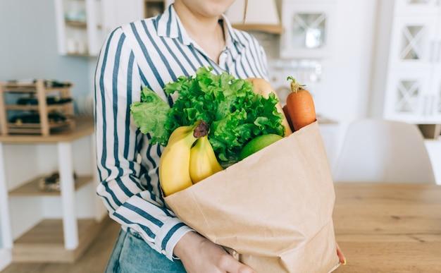 Mulher caucasiana segura sacola de compras eco com legumes frescos e baguete na cozinha moderna em casa.