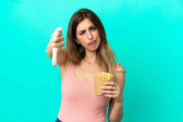 Mulher caucasiana segurando chips fritos isolados na parede azul, mostrando o polegar para baixo com expressão negativa