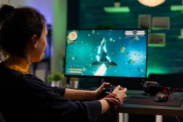 Mulher caucasiana, segurando o joystick sem fio e jogando videogame virtual. transmissão virtual cibernética realizando torneio ao vivo usando equipamento profissional em um estúdio doméstico de jogos