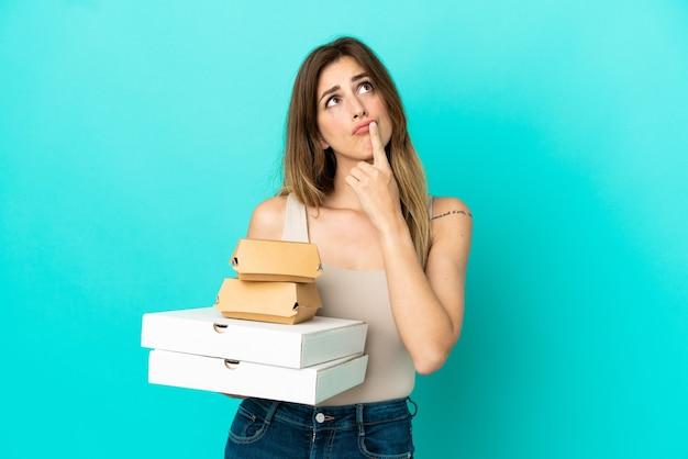 Mulher caucasiana segurando pizzas e hambúrguer isolados em um fundo azul, tendo dúvidas enquanto olha para cima