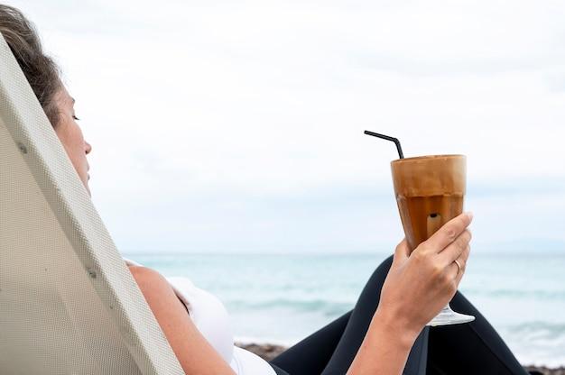 Mulher caucasiana segurando uma bebida de café em uma praia com espuma e canudo com o mar