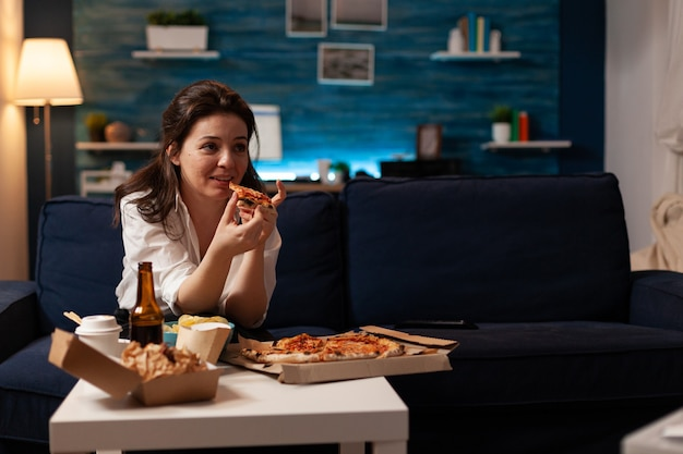 Mulher caucasiana segurando uma deliciosa fatia de pizza comendo comida para viagem