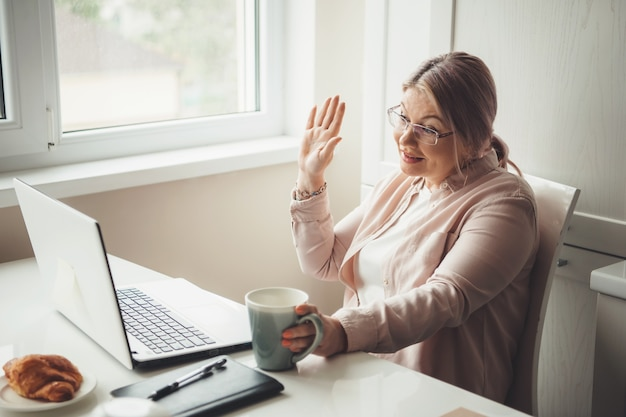 Mulher caucasiana sênior cumprimentando alguém no laptop, tendo uma reunião online enquanto bebe um chá com croissant