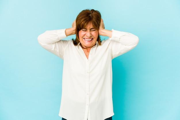 Mulher caucasiana sênior isolada cobrindo as orelhas com as mãos, tentando não ouvir o som muito alto.