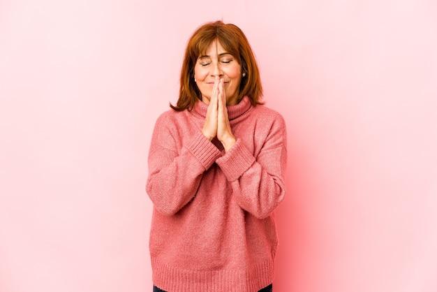 Mulher caucasiana sênior isolada de mãos dadas orando perto da boca, sente-se confiante.