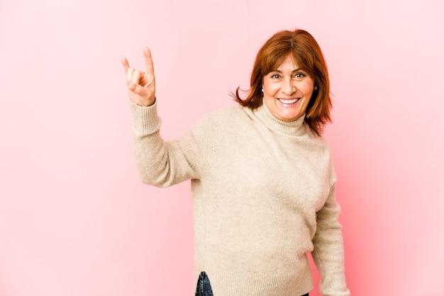 Mulher caucasiana sênior isolada mostrando um gesto de chifres como um conceito de revolução.