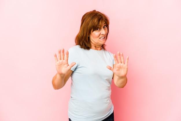 Mulher caucasiana sênior isolada rejeitando alguém mostrando um gesto de nojo.