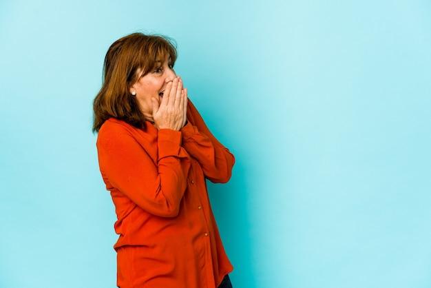 Mulher caucasiana sênior isolada rindo de algo, cobrindo a boca com as mãos.