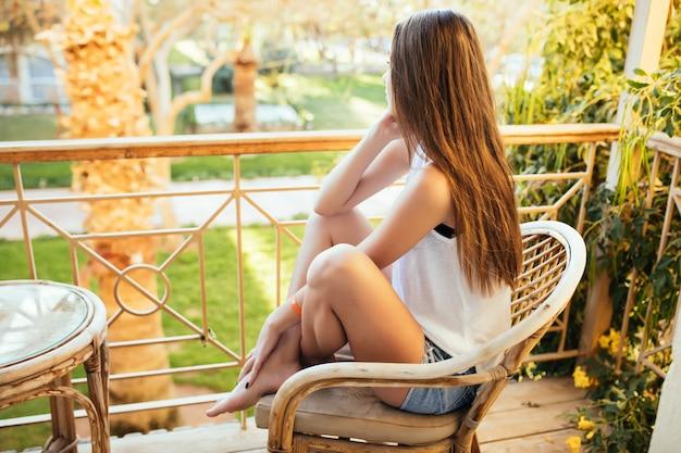Mulher caucasiana sentada e relaxando na varanda de um hotel