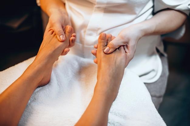 Mulher caucasiana sentada em um sofá do spa e fazendo massagem nos pés em um centro moderno e saudável
