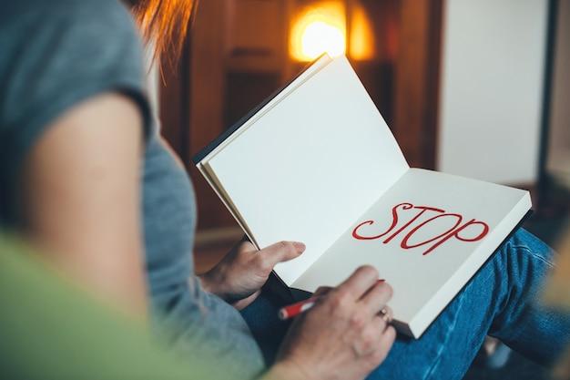 Mulher caucasiana sentada no sofá e escrevendo stop no livro com caneta vermelha