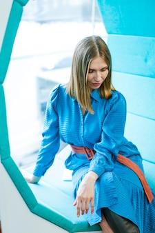 Mulher caucasiana, sentada perto da janela no banco em forma de círculo com vestido azul no fundo do ...