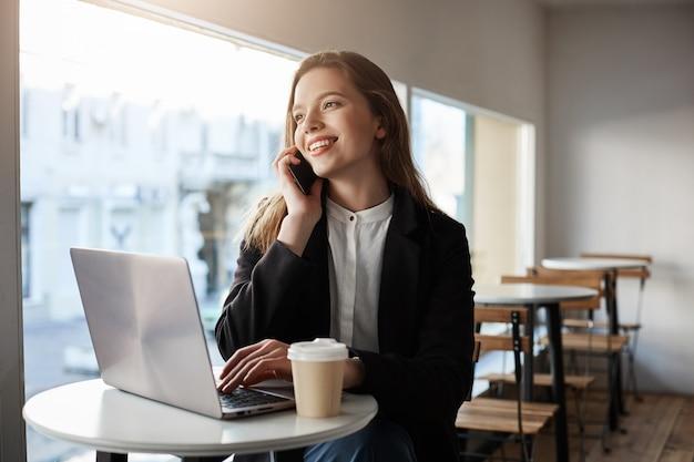Mulher caucasiana, sentado no café com laptop, tomando café, falando no smartphone